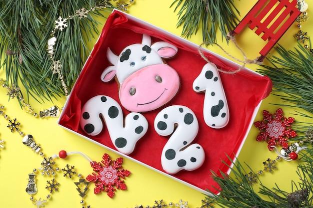 Peperkoekkoekjes in de vorm van nummers 2021 en stier, geschenken op kerstmis of noel-vakantie, gelukkig nieuwjaar, gele achtergrond. uitzicht van boven