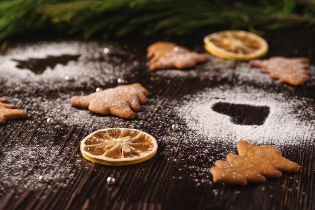 Peperkoekkoekjes in kerstboom en hartvorm, poedersuiker op houten tafel, citrus gedroogd fruit, sparrentak, hoekmening, selectieve aandacht