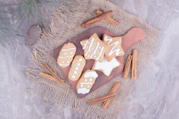 Peperkoekkoekjes in ster en ovale vormen met pijpjes kaneel op houten schotel.