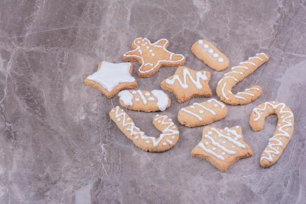 Peperkoekkoekjes in ster-, stok- en ovale vormen op marmer.