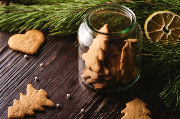 Peperkoekkoekjes kerstboom en hartvorm in glanzende glazen pot op houten tafel, citrus gedroogde citroen, dennenboomtak, hoekmening, selectieve aandacht