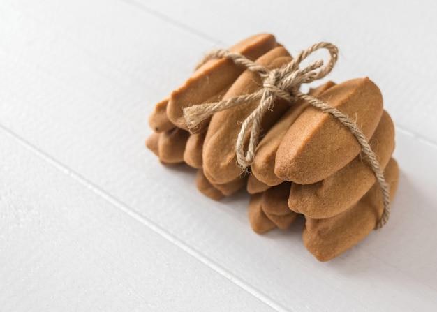 Peperkoekkoekjes met de hand op een witte houten lijst.