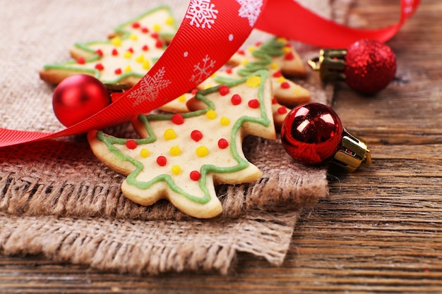 Peperkoekkoekjes met kerstversiering op jutedoek en houten tafel
