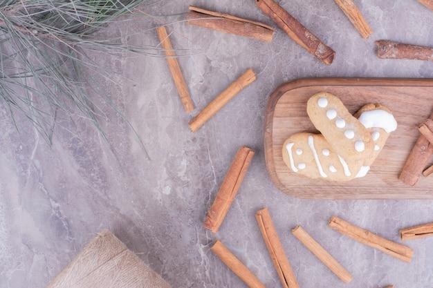 Peperkoekkoekjes met pijpjes kaneel op lange houten raad.