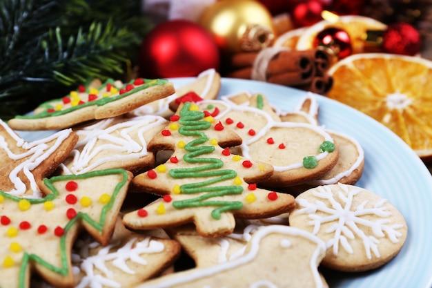 Peperkoekkoekjes op bord met kerstversiering op houten tafel