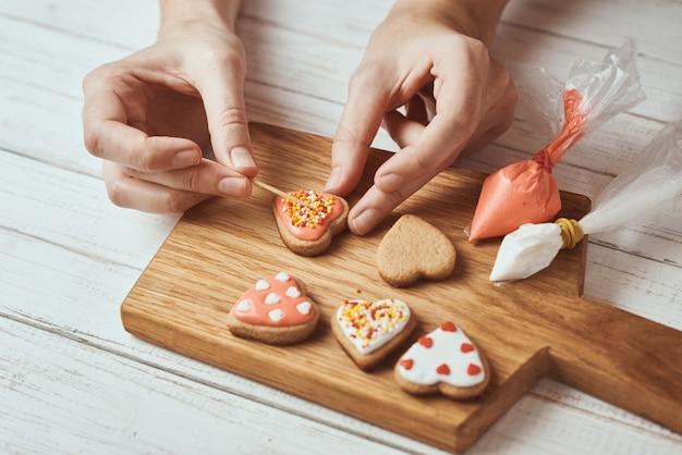 Peperkoekkoekjes versieren met glazuur. de vrouwenhanden verfraaien koekjes in vorm van hart, close-up