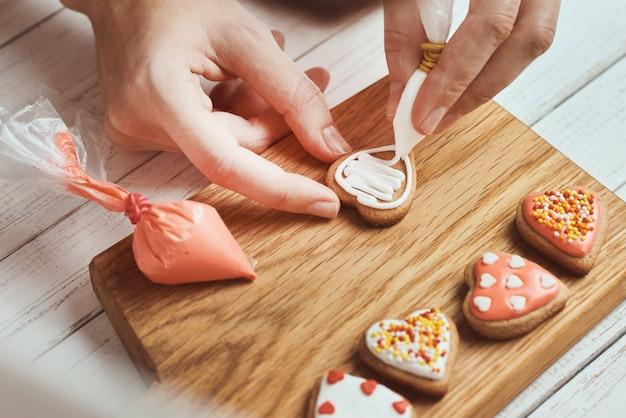 Peperkoekkoekjes versieren met glazuur.