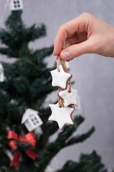 Peperkoekkoekjes voor kerstversiering. kerst gebakken goederen in vrouwelijke hand. kerstboom op achtergrond.