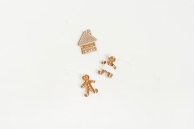 Peperkoekman, vrouw en huiskoekjes die op witte oppervlakte worden geïsoleerd. plat lag, bovenaanzicht