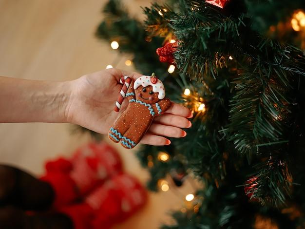 Peperkoekmannetje in de handen van het meisje op de achtergrond van de kerstboom