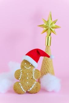 Peperkoekmannetje in een kerstmuts met een kerstboom gemaakt van een wafelkegel op een roze