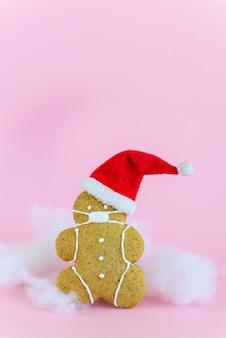 Peperkoekmannetje in een masker en kerstmuts op een roze.