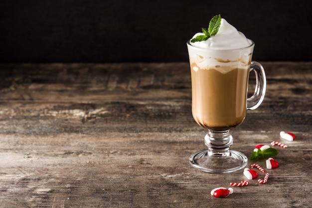 Pepermunt koffie mokka voor kerstmis op houten tafel en zwart