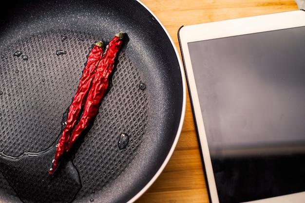 Pepers in een koekenpan en tablet