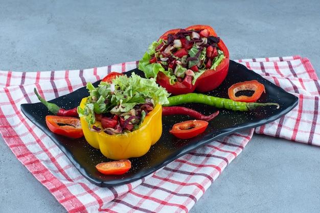 Peperschotel met kleine salade porties op marmeren tafel.
