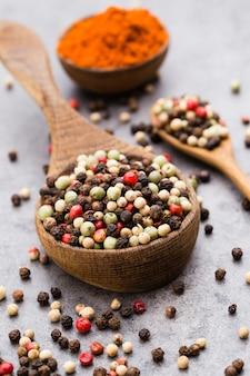 Peppercorn mix in een houten kom op grijze tafel.