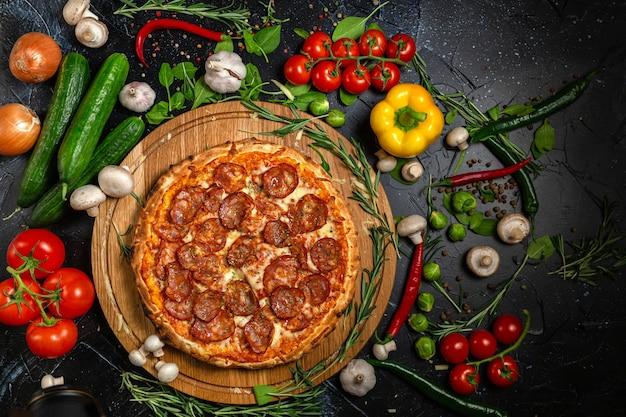 Pepperoni pizza en koken ingrediënten tomaten basilicum op zwarte betonnen achtergrond. bovenaanzicht van hete pepperoni pizza.