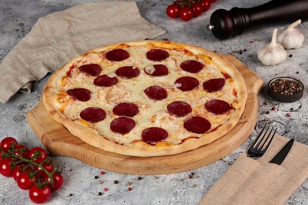 Pepperoni pizza, houten plank, grijze achtergrond
