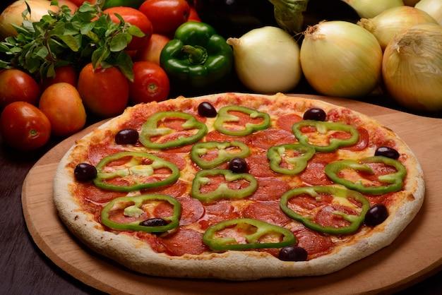 Pepperoni pizza met groene paprika's op een houten bord en groenten op de achtergrond.