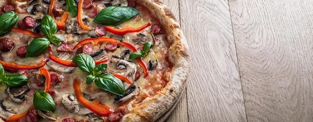 Pepperoni-pizza met jagersworsten, champignons, rode pepers en verse basilicum op een houten tafel
