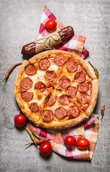 Pepperoni pizza met salami en tomaten op de stenen tafel