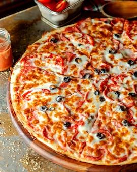 Pepperoni pizza met tomaat en olijven