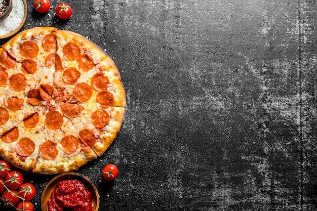 Pepperoni-pizza met tomaten, kruiden en tomatenpuree. op donkere rustieke achtergrond