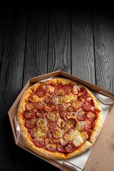 Pepperoni pizza op donker zwart houten bord, bovenaanzicht, plaats voor tekst, traditionele italiaanse pizza