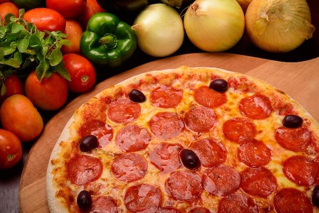 Pepperoni pizza op een houten bord en groenten op de achtergrond
