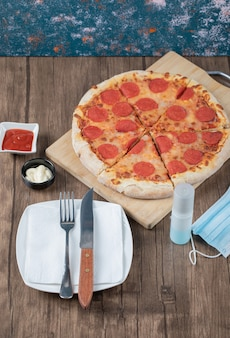 Pepperoni-pizza op een houten bord met sauzen, bord, handdesinfecterend middel en masker eromheen