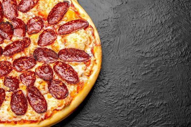 Pepperoni pizza op een zwarte achtergrond, op basis van tomaten met mozzarella en pikante salami napoli op een houten standaard