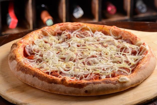 Pepperoni worst pizza met ui op een houten plank braziliaanse pizza
