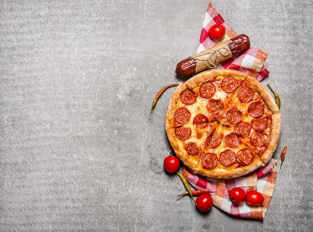 Pepperonipizza met salami en tomaten. op de stenen tafel. vrije ruimte voor tekst. bovenaanzicht Premium Foto