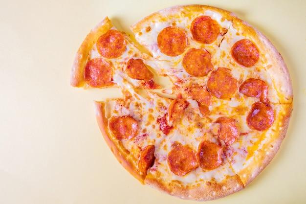 Pepperonispizza op een gele achtergrond.