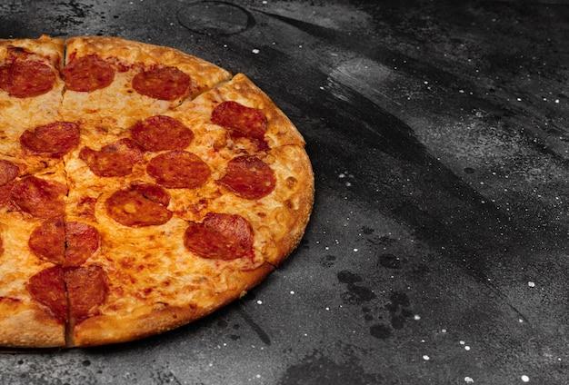 Pepperonispizza op zwarte concrete achtergrond. bovenaanzicht met kopie ruimte.