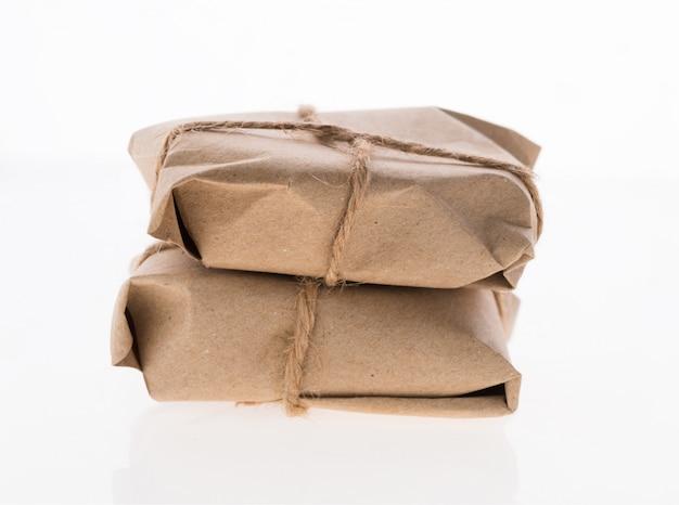 Percelen dozen omwikkeld met gerecycled papier en vastgebonden met jute touw geïsoleerd op wit