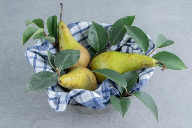 Peren en bladeren in een kom bedekt met een handdoek op marmer