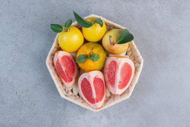 Peren en grapefruitplakken in een witte mand op marmeren achtergrond.