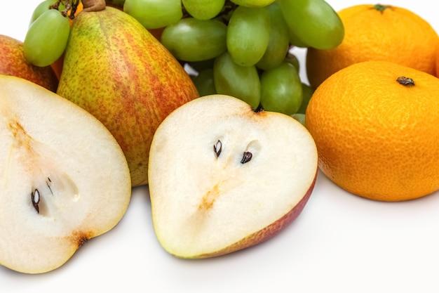 Peren, mandarijnen en druiven op een witte achtergrond kopie ruimte foto