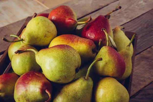 Peren met waterdruppels. peren oogsten. fruit achtergrond. verse biologische peren, selectieve aandacht. sappige smaakvolle peren van rustieke achtergrond. vrije ruimte voor tekst. herfst natuur concept.