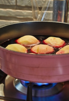 Peren worden gekookt in rode siroop met wijn op gasfornuis.