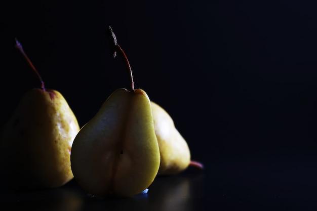 Perenschijfjes op een zwarte background.pears in een bord en plakjes peren bovenaanzicht.
