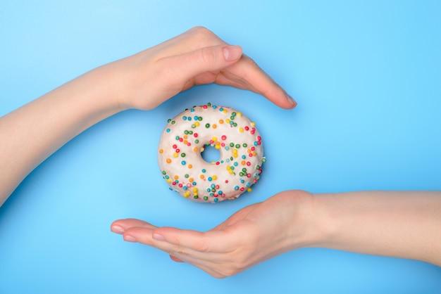 Perfect concept voor het creëren van eten. foto van smakelijke donut met kleurrijke hagelslag en twee handen die dak maken die het vliegende voorwerp vangen dat over de achtergrond van het pastelkleur rerto patroon wordt geïsoleerd