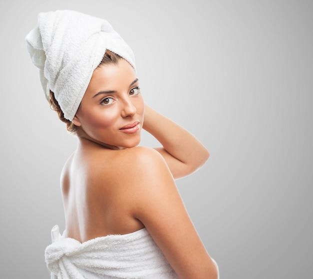 Perfect dame in handdoek lachend over schouder