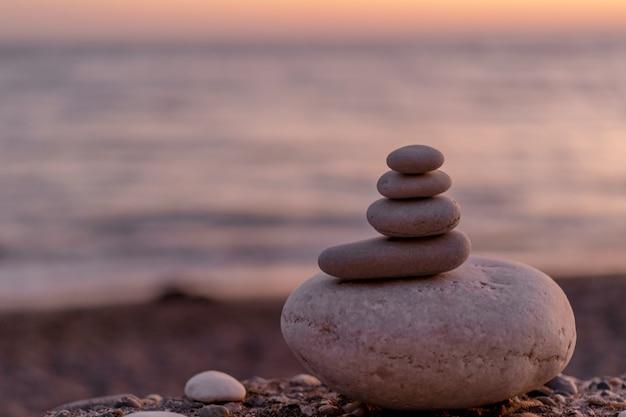 Perfect evenwicht van gestapelde kiezelstenen bij kust naar zonsondergang.
