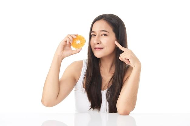 Perfect frisse huid portret van het jonge aziatische mooie meisje met stukjes sinaasappel in de hand geïsoleerd op een witte achtergrond