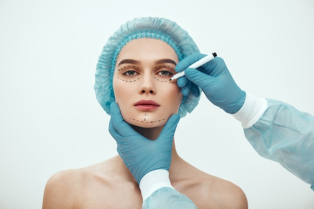 Perfect gezicht mooie en jonge vrouw in blauwe medische hoed die wacht op gezichtschirurgie terwijl