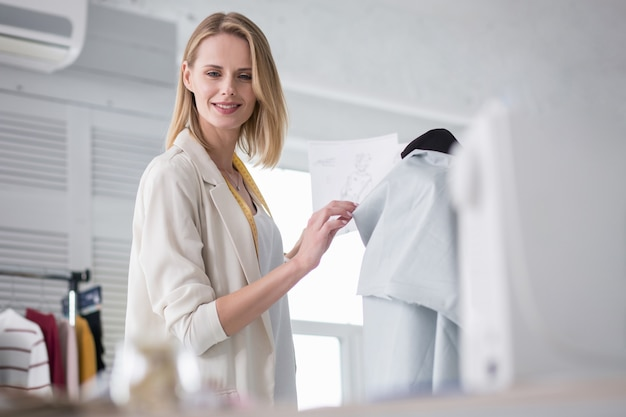Perfect kledingstuk. mijmende vrouwelijke couturier die schetsen gebruikt tijdens het werken met stof