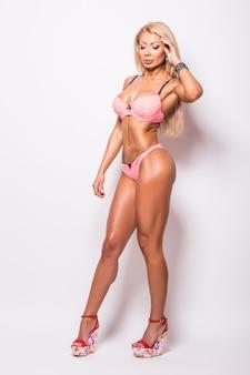 Perfect lichaam fitness vrouw bodybuilder in roze swimsuit poseren over wit in de studio.