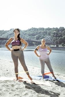 Perfect lichaam. gelukkige actieve vrouwen die op het strand oefenen terwijl ze proberen af te vallen